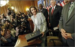 Speaker of the House, Rep. Nancy Pelosi, D-Calif., center, picks up the financial rescue package sent to the White House for President Bush to approve, Friday, Oct. 3, 2008 in Washington. (AP Photo/Pablo Martinez Monsivais)
