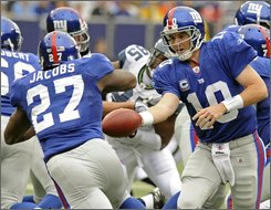 New York Giants quarterback Eli Manning, right, hands the ball off to running back Brandon Jacobs during the first quarter of an NFL football game against the Seattle Seahawks Sunday, Oct. 5, 2008 at Giants Stadium in East Rutherford, N.J.  The Giants beat the Seahawks 44-6. (AP Photo/Bill Kostroun)