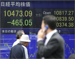 A pedestrian is reflected on a stock indicator in Tokyo, Japan, Monday, Oct. 6, 2008. Japan's benchmark Nikkei 225 stock average fell sharply in the morning. (AP Photo/Shizuo Kambayashi)