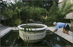 An Israeli man cleans out a small pool at Sergei's Courtyard in Jerusalem, in this Monday, Oct. 6, 2008.  Russia is to take-over the small tract of land known as Sergei's Courtyard, with Israeli Prime Minister Ehud Olmert's Cabinet agreeing to the hand over Sunday Oct. 5, 2008, amid serious policy differences that have sprung up between the two countries. The Russians are to take ownership of the property which once accommodated Russian pilgrims visiting the Holy Land and now houses offices of Israel's Agriculture Ministry and the Society for the Protection of Nature in Israel. (AP Photo/Tara Todras-Whitehill)