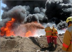 In this Sept. 14, 2004 file photo, fire fighters try to contain an oil pipeline fire after an attack by insurgents near Beiji, 250 kilometers (155 miles) north of Baghdad, Iraq. Representatives of 35 international oil companies will meet with Iraqi government officials in London on Monday to discuss the bidding process for eight enormous oil and gas fields. If the contracts are approved, they could lead to the biggest foreign stake in Iraq since the industry was nationalized more than 30 years ago.(AP Photo/Yahaya Ahmed)