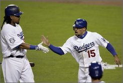 Los Angeles Dodgers' Rafael Furcal (15) is congratulated by Manny Ramirez after scoring on a double by Russell Martin during the fifth inning of Game 3 of baseball's National League division series in Los Angeles, Calif., Saturday, Oct. 4, 2008. (AP Photo/Francis Specker)