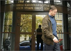 A Man leaves MICEX, Moscow Interbank Currency Exchange, Wednesday, Oct. 8, 2008, in Moscow. Trading on both Russian stock markets were halted, on one until Friday and on the other, until further notice on Wednesday after shares plunged within an hour of opening on fears the credit crisis will take a heavy toll on growth. (AP Photo/Mikhail Metzel)