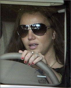In this  Oct. 11, 2007, file photo, singer Britney Spears drives from family court in Los Angeles.  Spears may have to stand trial for a misdemeanor driving without a license after all. A three-judge panel in Los Angeles on Tuesday denied a motion by Spears' attorney seeking a delay in the trial and a possible reduction in the charge. (AP Photo/Mark J. Terrill, file)