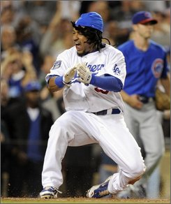 Los Angeles Dodgers' Manny Ramirez reacts after sliding safely into home to score on a two-run double by James Loney during the first inning of Game 3 of baseball's National League division series in Los Angeles, Calif., Saturday, Oct. 4, 2008. Ramirez and the Dodgers shoved Chicago into another long winter Saturday night, completing a three-game sweep of their first-round playoff series with a 3-1 victory.  (AP Photo/Mark J. Terrill)