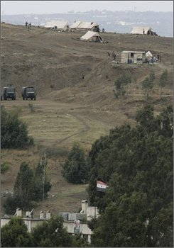 "Syrian soldiers are seen near vehicles and tents they erect as part of their troop buildup on the Syrian side along Lebanon's northern Abboudiyeh border crossing, Lebanon, Tuesday, Oct. 7, 2008. The recent Syrian troop buildup has Lebanese anti-Syrian politicians worried that Damascus could intervene militarily in Lebanon. The U.S. State Department on Monday said it was concerned by the Syrian military activity. ""Any intervention by Syrian troops into Lebanon would be unacceptable,"" deputy spokesman Robert Wood told reporters in Washington. (AP Photo/Hussein Malla)"