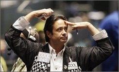In this Sept. 30, 2008 file photo, trader Bryan Cooley watches the markets in the S&P 500 futures trading pit at the CME Group in Chicago. (AP Photo/M. Spencer Green, File)