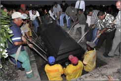 Friends, relatives and cemetery workers lower the coffin of Jose Luis Garza, 47, in Monterrey, Mexico, Tuesday, Oct. 7, 2008. Garza, who weighed 450-kilograms, 990-pounds, and who had earlier appealed on Mexican television for help tackling his weight problem, died Tuesday Oct. 7, 2008 of heart failure, his family said. (AP Photo/Monica Rueda)