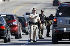 Law enforcement personnel work at a checkpoint Thursday, Oct. 9, 2008, in O'Fallon, Mo., as they search for a man suspected in the drive-by slaying of a 12-year-old boy who investigators said died while doing school work in his home on Tuesday. After a manhunt lasting several hours, Marcus Powell, 27, was found in a shed at the Runny Meade Estates mobile home park and taken into custody. (AP Photo/Jeff Roberson)