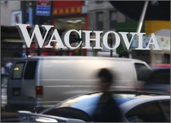 A Sept. 29, 2008 file photo shows a person is reflected in the window of a Wachovia Corp. branch office in New York. Federal officials continued their fervent quest Thursday, Oct. 9, 2008, to reach an agreement between Citigroup and Wells Fargo over the fate of Wachovia Corp. -- which could include the splitting up of the bank. (AP Photo/Peter Morgan/file)