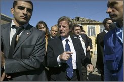 French Foreign Minister Bernard Kouchner, center, visits the town of Tkviavi, some 90 km (55.9 miles) from Tbilisi, Georgia, Friday, Oct. 10, 2008. French Foreign Minister Bernard Kouchner has visited damaged Georgian villages near separatist South Ossetia, in a show of European support for the pro-Western nation following its war with Moscow. (AP Photo/Shakh Aivazov)