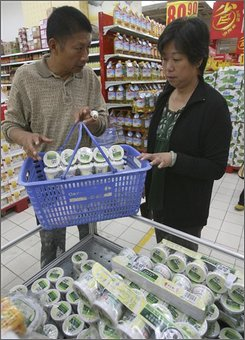 A Chinese couple buy yogurt at a supermarket in Wuhan in central China's Hubei province Thursday, Oct. 9, 2008. More than 10,000 children remain hospitalized after being sickened in China's tainted milk scandal, officials said, as the government released its first rules on allowable levels of the chemical blamed in the ailments. (AP Photo)