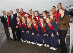 President Bush, far left, and first lady Laura Bush, far right, poses for a photo with members of the  2008 Little League Softball World Series Champions, during their arrival at Charleston Air Force Base, Friday, Oct. 10, 2008 in Charleston, S.C. The team is from Simpsonville, S.C. (AP Photo/Pablo Martinez Monsivais)