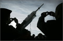 People take photos of the fixed vertical Russian Soyuz TMA-13 space ship that will carry new crew members to the international space station, at the launch pad in Baikonur Cosmodrome, Kazakhstan, Friday, Oct. 10, 2008.  The rocket is scheduled to blast off on Sunday, October 12.  (AP Photo/Dmitry Lovetsky)