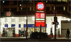 """A bicyclist on a night-time ride pauses next to a Conoco Phillps 76 gas station Thursday, Oct. 9, 2008 in Seattle.  """"We've been through almost eight years of continuously rising gasoline prices,"""" said AAA spokesman Geoff Sundstrom. """"Any notion that this is a temporary thing has pretty well been erased as a point of view among most consumers."""" (AP Photo/Ted S. Warren)"""