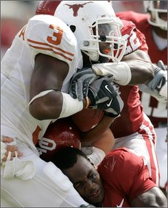 Oklahoma defensive back Nic Harris (5) loses his helmet while trying to tackle Texas running back Chris Ogbonnaya (3) during the third quarter of an NCAA college football game, Saturday, Oct. 11, 2008, in Dallas. (AP Photo/Tony Gutierrez)