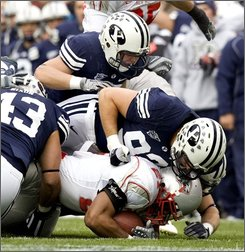 New Mexico tailback Rodney Ferguson (21) is taken down by four BYU players during the first quarter of an NCAA college football game Saturday, Oct. 11, 2008, in Provo, Utah. (AP Photo/Douglas C. Pizac)