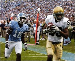 North Carolina's Kendric Burney (16) follows Notre Dame's Golden Tate (23) into the end zone for Notre Dame's first touchdown in the first half of a NCAA college football game Oct. 11, 2008, Chapel Hill, N.C.  (AP Photo/Sara D. Davis)
