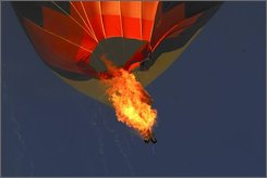 Blazing fuel tanks hang from a hot-air balloon that slammed into power lines during the Albuquerque International Balloon Fiesta in Bernaillo, N.M. on Friday, Oct. 10, 2008. The balloon scattered debris across the town as it disintegrated, killing one man and injuring another. (AP Photo/Terri Bordelon)