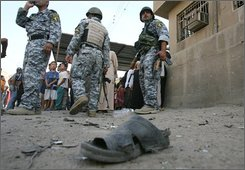 A shoe of one of the victims, is seen, on the ground as Iraqi forces stand guard the area after a car bomb explosion in the predominantly Shiite Bayaa district, southwestern Baghdad, iraq, on Sunday, Oct. 12, 2008. The bomb exploded Sunday in a commercial street of Baghdad killing seven people and wounding nine others, police said. (AP Photo/Hadi Mizban)