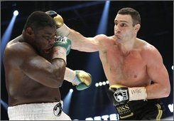 Vitali Klitschko, right, from Ukraine hits Samuel Peter, left, from Nigeria during a WBC heavyweight boxing world championship fight in Berlin, Germany, Saturday, Oct. 11, 2008. Klitschko won the fight after round nine due to technical knock out. (AP Photo/Herbert Knosowski)