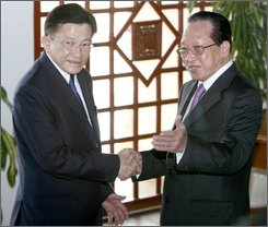 Cambodian Foreign Minister Hor Namhong, right, shakes hands  with his Thai counterpart, Sompong Amornwiwat, left, on the arrival at Cambodian Ministry of Foreign Affair in Phnom Penh, Cambodia, Monday, Oct. 13, 2008. Cambodian and Thai foreign ministers resumed talks Monday on lingering military tension along their border that recently erupted into a clash between the troops. (AP Photo/Heng Sinith)
