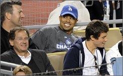 Golfer Tiger Woods watches the game the sixth inning in Game 3 of the National League baseball championship series between the Los Angeles Dodgers and Philadelphia Phillies Sunday, Oct. 12, 2008, in Los Angeles. (AP Photo/Kevork Djansezian)