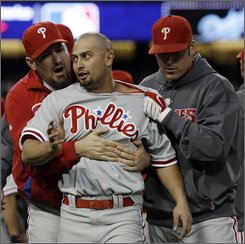 Philadelphia Phillies' Shane Victorino is held back by teammates during a bench-clearing incident during the third inning in Game 3 of the National League baseball championship series against the Los Angeles Dodgers Sunday, Oct. 12, 2008, in Los Angeles. (AP Photo/David J. Phillip)