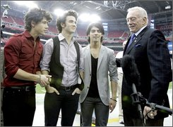 From Left, Musicians Nick Jonas, Kevin Jonas, Joe Jonas and Dallas Cowboys' owner Jerry Jones stand along the sidelines Sunday, Oct. 12, 2008 in Glendale, Ariz. prior to the Arizona Cardinals/Dallas Cowboys football game. (AP Photo/Paul Connors)