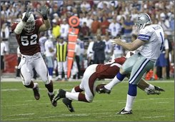 Dallas Cowboys' Mat McBriar (1) has his punt blocked by Arizona Cardinals' Sean Morey as Monty Beisel (52) looks on during overtime of an NFL football game Sunday, Oct. 12, 2008 in Glendale, Ariz. Beisel picked up the block and scored the game-winning touchdown to defeat the Cowboys 30-24. (AP Photo/Paul Connors)
