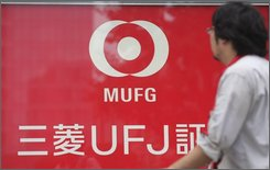 In this Sept. 22, 2008 file photo, a pedestrian walks past a signboard of Mitsubishi UFJ Financial Group Inc., in Tokyo. Morgan Stanley completed a deal Monday to receive a $9 billion investment from Japanese bank Mitsubishi UFJ Financial Group Inc., giving it a much-needed cash infusion.  (AP Photo/Shizuo Kambayashi, file)