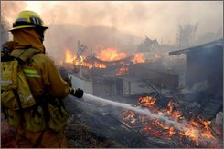 A firefighter battles flames at a mobile home park early Monday morning, Oct. 13, 2008, north of Los Angeles after intense Santa Ana winds swept into Southern California and whipped up a 3,700-acre wildfire. (AP Photo/Mike Meadows)