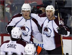 Colorado Avalanche's Ryan Smyth, right, celebrates his goal with Paul Stastny, left, and Joe Sakic, bottom, during second period NHL hockey action against the Calgary Flames in Calgary, Alberta on Tuesday, Oct. 14, 2008.  (AP Photo/The Canadian Press, Larry MacDougal)