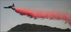 In this July 19, 2004 file photo, a C-130 air tanker drops a flame-retardant slurry on a wildfire in the hills above Sylmar, Calif. Despite pressure from elected officials and the military, the Bush administration has yet to outfit similar California Air National Guard cargo planes for firefighting -- a delay that could have grave implications as the state confronts the worst of its wildfire season. (AP Photo/Gene Blevins, file)