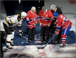"Montreal Canadiens captain Saku Koivu, right, and Boston Bruins captain Zdano Chara, left, take the ceremonial face off from the two oldest surviving Montreal Canadiens players Elmer Lach, second left, and Emile ""Butch"" Bouchard as the Canadiens begin their 100th season at home in NHL hockey action in Montreal Wednesday, Oct. 15, 2008.  (AP Photo/The Canadian Press, Ryan Remiorz)"