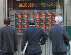 Pedestrians watch an electric market board in Tokyo, Thursday, Oct. 16, 2008. Japan's key stock index plunged more than 10 percent in early trade Thursday, hit by another dive on Wall Street and growing recession fears. (AP Photo/Katsumi Kasahara)
