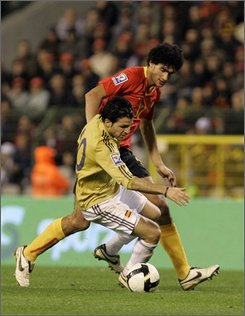 Spain's Cesc Fabregas, forground, is challenged by Marouane Fellaini of Belgium, during their World Cup group 5 qualifying soccer match in Brussels, Wednesday Oct. 15, 2008. (AP Photo/Yves Logghe)
