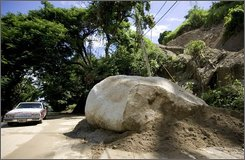 A car passes by a large boulder which tumbled into a road along with a mudslide the previous night due to heavy rains from the Hurricane Omar storm system in Yabucoa, eastern Puerto Rico, Thursday, Oct. 16, 2008. Puerto Rico was largely spared the effects of Hurricane Omar, which veered east of the U.S. Territory, and was quickly moving away from the northern Leeward Islands Thursday after crossing over them as a major Category 3 storm. (AP Photo/Brennan Linsley)