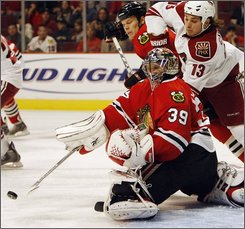Chicago Blackhawks goalie Nikolai Khabibulin(39), of Russia, blocks the puck past  Phoenix Coyotes' Daniel Carcillo (13) during the first period of an NHL hockey game Wednesday, Oct. 15, 2008, in Chicago. (AP Photo/Nam Y. Huh)