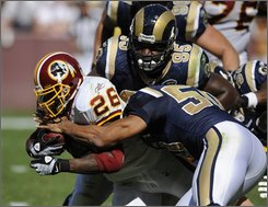 Washington Redskins running back Clinton Portis (26) is tackled by St. Louis Rams linebacker Pisa Tinoisamoa (50) and defensive tackle Clifton Ryan (95) during the second quarter of an NFL football game, Sunday, Oct. 12, 2008 in Landover, Md. The Rams won 19-17. (AP Photo/Nick Wass)