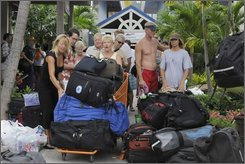 British Virgin Island vacationer Nemira Stauskas, center, of San Diego, Calif. removes her belongings from The Moorings Marina, in Roadtown, Tortola, British Virgin Islands, Wednesday Oct. 15, 2008. All vacationers at the marina were evacuated from their boats to hotels around the island in preparation for Hurricane Omar. (AP Photo/Don Petersen)