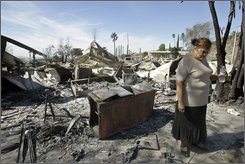 Mariam Villarreal, 65, views what remains of her former home Wednesday, Oct. 15, 2008, which was destroyed by a wildfire at the Sky Terrace Mobile Lodge, in the Lake View Terrace section of Los Angeles. (AP Photo/Ric Francis)