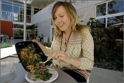 "Vegan foodist Margaret Oakley prepares her lunch outside the Santa Monica Public library Friday Oct. 17, 2008 in Santa Monica, Calif. Oakley is part of the ""Living Library"" project where patrons can ""check out"" one of 14 people for up to 30 minutes to engage them in conversation. Other living books include people involved in nudism, Buddhism and foodism.   (AP Photo/Nick Ut)"