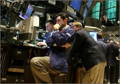 A Specialist looks at the monitor as he waits for the closing bell to ring on the trading floor at the New York Stock Exchange in the afternoon hours as the Dow is heading down Friday, Oct.  17,  2008  (AP Photo/David Karp)