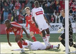 Toronto FC's Rohan Ricketts, left, peels away after scoring his side's second goal as Chicago Fire's goalkeeper Jon Busch, right, reacts during first half MLS soccer action in Toronto on Saturday, Oct. 18,2008. (AP Photo/The Canadian Press, Chris Young