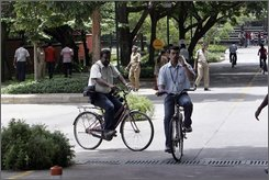 Visitors and employees of Infosys Technologies ride bicycles inside the company's campus at Electronic City in Bangalore, India, Friday, June 6, 2008. Bangalore, the capital of Indian outsourcing, is perhaps the closest India comes to Wall Street. Now that proximity, which has fueled years of growth and transformed the city into one of India's most cosmopolitan, has put Bangalore on edge.  (AP Photo/Aijaz Rahi)