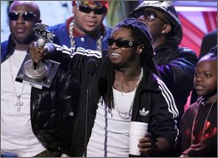 Lil Wayne, center, accepts the MVP of the Year award during the BET Hip Hop Awards '08, Saturday Oct. 18, 2008, in Atlanta. (AP Photo/John Amis)