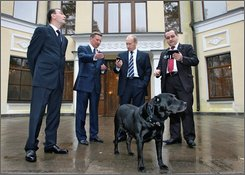 Wearing a collar containing satellite-guided positioning equipment dog Koni stands in front of his owner Russia's Prime Minister Vladimir Putin, 2nd from  right, in Putin's Novo-Ogaryovo residence outside Moscow, on Friday, Oct. 17, 2008.  Shown from right are