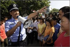  A Chinese police officer urges hundreds of workers to leave as they gather outside a large toy factory in Zhang Mu Tou of Guangdong province, of southern China Friday, Oct. 17, 2008. Hundreds of workers protested Friday for a third straight day outside the large toy factory that closed in southern China amid a global slowdown that has begun hurting Chinese manufacturers. (AP Photo/Vincent Yu)