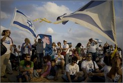 Israelis, carrying Israeli flags and posters with portraits of Israeli soldier, Cpl. Gilad Schalit, participate in a rally calling for his release near the place where he was captured close to the Gaza Strip border in Kerem Shalom southern Israel, Sunday Oct. 19, 2008. Schalit was captured in a June 25, 2006 raid by militants who tunneled under the Gaza-Israel border and attacked an Israeli army post, killing two soldiers and taking Schalit with them. (AP Photo/Sebastian Scheiner)